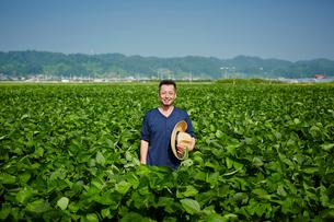 畑の中に立つ農夫の写真素材 [FYI02058222]