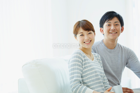 ソファに座る若いカップルの写真素材 [FYI02058226]