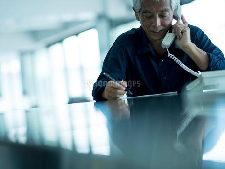 メモしながら電話するシニア男性の写真素材 [FYI02058231]