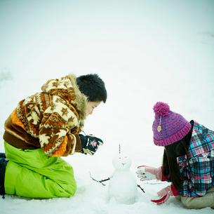 雪だるまを作る男の子と女の子の写真素材 [FYI02058233]