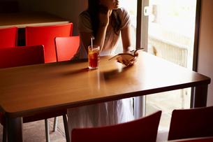 本を持ち窓の外を眺める女性の写真素材 [FYI02058239]