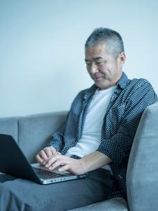 ノートパソコンを操作するミドル男性の写真素材 [FYI02058245]