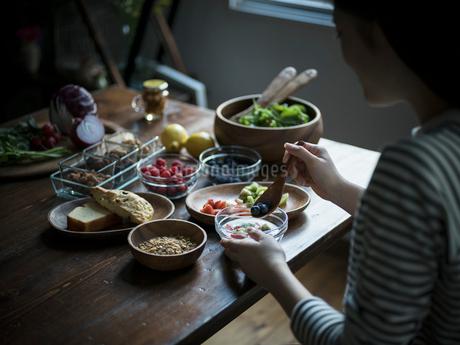 フルーツグラノーラヨーグルトを食べる女性の写真素材 [FYI02058269]