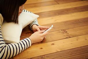 床に寝転びスマートフォンを操作する10代女性の写真素材 [FYI02058270]