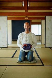 風呂敷包みを持って正座する外国人男性の写真素材 [FYI02058279]
