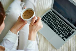 コーヒーを持ちノートパソコンを見る女性の写真素材 [FYI02058291]