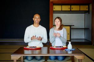 和室で日本酒を楽しむ外国人カップルの写真素材 [FYI02058322]