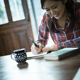 書き物をする女性の写真素材 [FYI02058340]