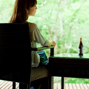 新緑と椅子に座った女性の後ろ姿の写真素材 [FYI02058343]