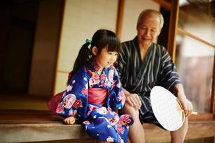 縁側に座る浴衣姿の女の子と祖父の写真素材 [FYI02058354]