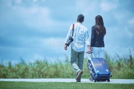 スーツケースをひいて歩くミドル夫婦の写真素材 [FYI02058364]