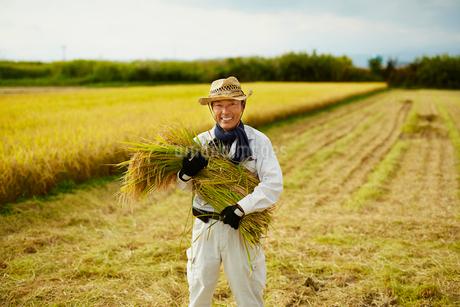 稲を抱える笑顔の農夫の写真素材 [FYI02058378]