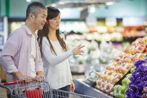 スーパーマーケットで買い物をする夫婦の写真素材 [FYI02058389]