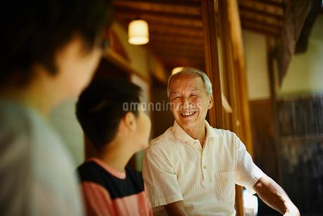 縁側で談笑する祖父母と孫の写真素材 [FYI02058411]