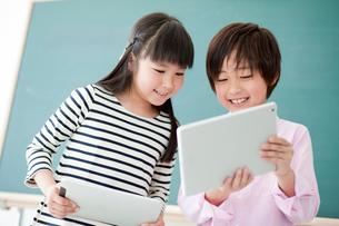 教室でタブレットPCを見る笑顔の小学生の女の子と男の子の写真素材 [FYI02058427]