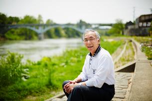川辺に座る笑顔のシニア男性の写真素材 [FYI02058473]