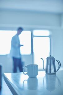 テーブルの上のコーヒーポットとカップと男性の写真素材 [FYI02058515]