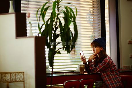 カフェでスマートフォンを見る女性の写真素材 [FYI02058516]