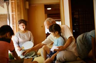 縁側でくつろぐ祖父母と孫たちの写真素材 [FYI02058520]