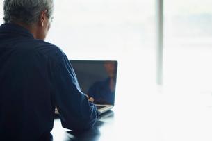 ノートパソコンを操作するシニア男性の写真素材 [FYI02058540]