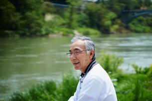 川を眺める笑顔のシニア男性の写真素材 [FYI02058573]