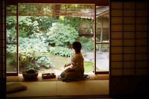 縁側に座り庭を眺めるシニア女性の写真素材 [FYI02058578]