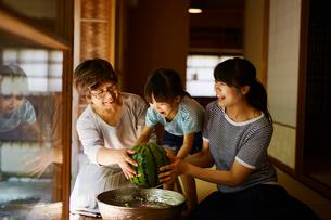 スイカを持ち上げる三世代女性ファミリーの写真素材 [FYI02058582]