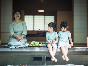 縁側に座る祖母と女の子2人の写真素材 [FYI02058588]