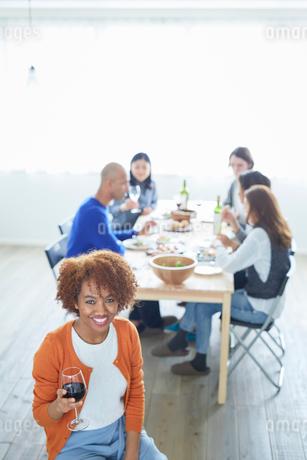 赤ワインを持つ外国人女性と食事をする仲間たちの写真素材 [FYI02058607]