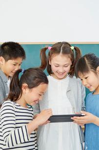 タブレットPCを見る日本人と外国人の子供たち4人の写真素材 [FYI02058623]
