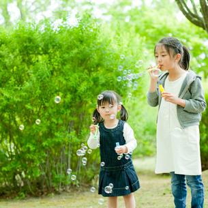 シャボン玉で遊ぶ2人の女の子の写真素材 [FYI02058630]