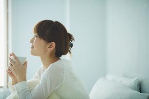 ベッドでコーヒーを飲む女性の写真素材 [FYI02058637]