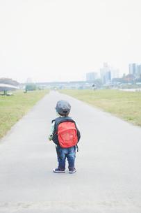 道に立つリュックを背負った男の子の後ろ姿の写真素材 [FYI02058645]