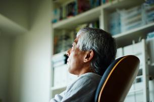 椅子に座るシニア男性の横顔の写真素材 [FYI02058653]