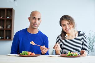 カリフォルニアロールを食べる外国人カップルの写真素材 [FYI02058663]