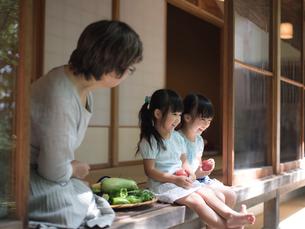 縁側に座る祖母と女の子2人の写真素材 [FYI02058670]