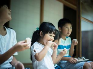 縁側でおにぎりを食べる子供たちの写真素材 [FYI02058693]