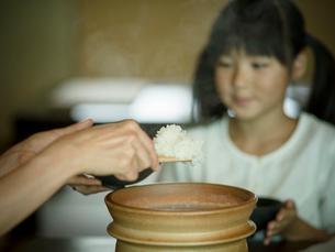 ご飯をよそう母親の手元と女の子の写真素材 [FYI02058760]