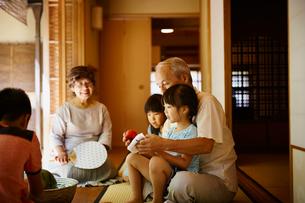 縁側でくつろぐ祖父母と孫たちの写真素材 [FYI02058779]