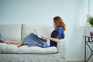 ソファの上でノートパソコンを操作する女性の写真素材 [FYI02058799]