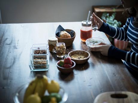 フルーツグラノーラヨーグルトを食べる女性の手元の写真素材 [FYI02058805]