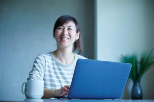 ノートパソコンと笑顔のミドル女性の写真素材 [FYI02058807]