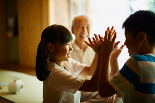 あやとりをする孫たちと笑顔の祖父の写真素材 [FYI02058827]