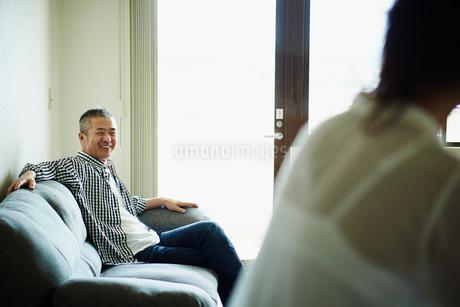 リビングルームでくつろぐミドル夫婦の写真素材 [FYI02058832]