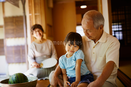 祖父に抱かれる女の子と見守る祖母の写真素材 [FYI02058837]