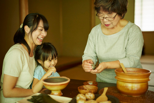 おにぎりを作る三世代女性ファミリーの写真素材 [FYI02058847]