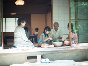 縁側でスイカを冷やす祖父母と孫たちの写真素材 [FYI02058870]