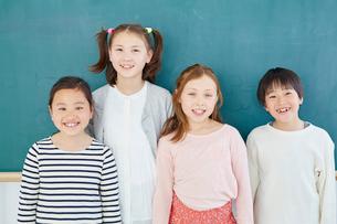 黒板の前に立つ日本人と外国人の子供たち4人の写真素材 [FYI02058874]