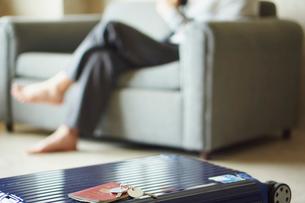 スーツケースとソファに座る男性の写真素材 [FYI02058875]