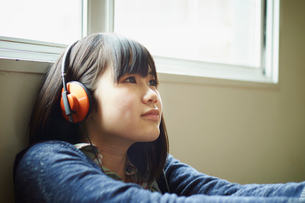 ヘッドフォンで音楽を聴く10代女性の写真素材 [FYI02058894]